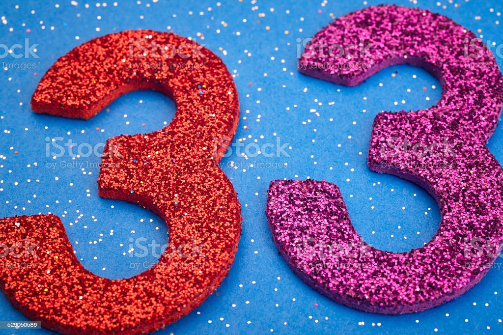 Number thirtythree red purple color over a blue background. Anni stock photo