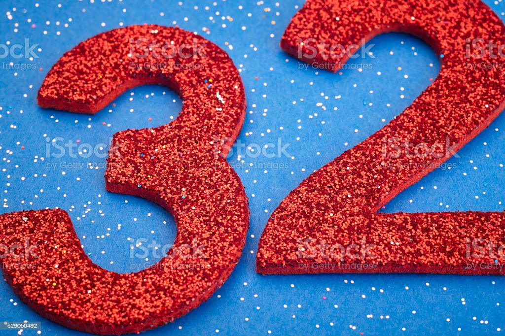 Number thirtytwo red color over a blue background. Anniversary stock photo