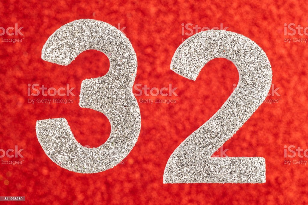 Number thirty-two silver color over a red background. Anniversary. stock photo