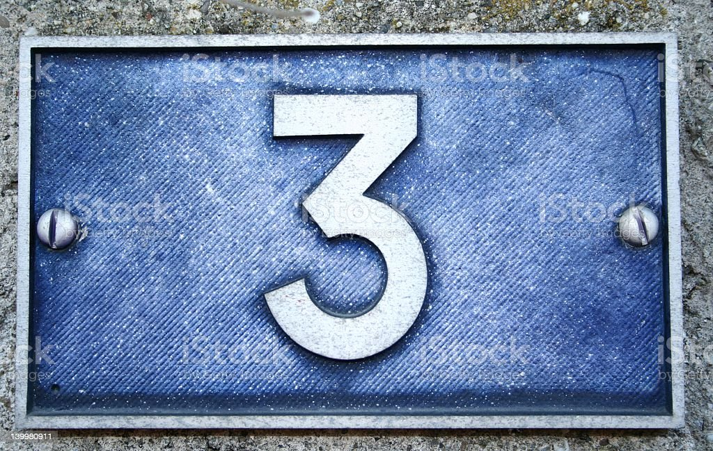 Number three plaque bolted onto a cement wall royalty-free stock photo