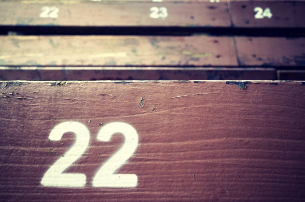 Number twenty two painted on an old wooden seat. stock photo