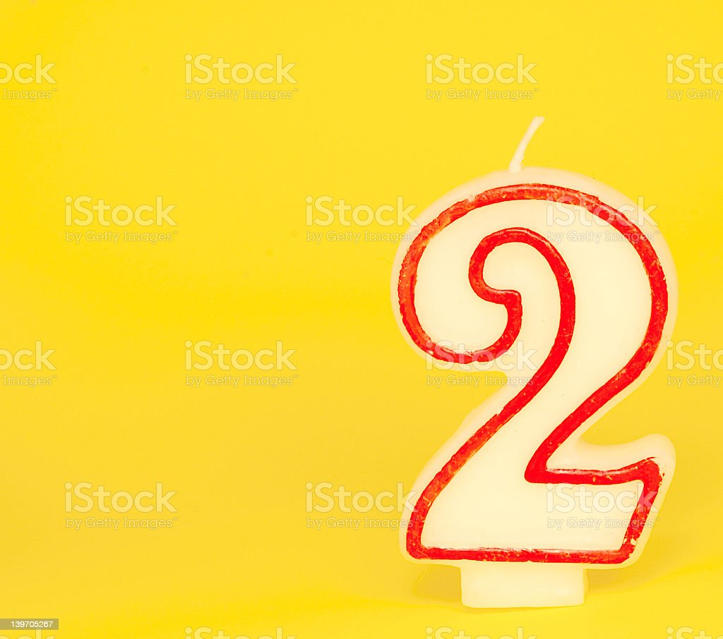 Number Two Candle on Yellow Background stock photo