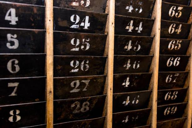 alt und verblasst stechuhr lochkarte wandgestell leer nummeriert - uhrenhalter stock-fotos und bilder
