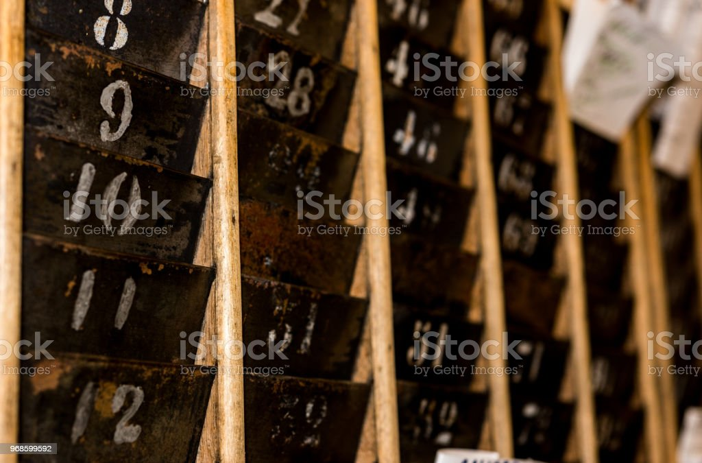 Numbered old and faded time clock punch card wall rack with paper in the distance stock photo