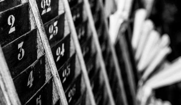 Numbered old and faded time clock punch card wall rack with papers in the distance stock photo