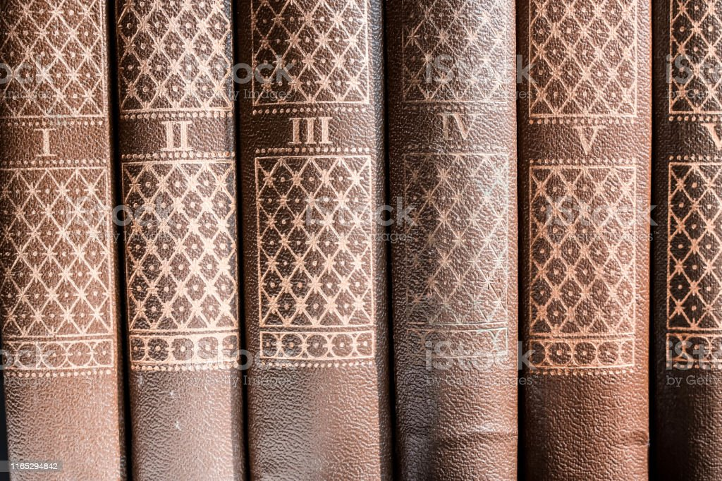 Series of brown hard cover binding books on library shelf with serial...