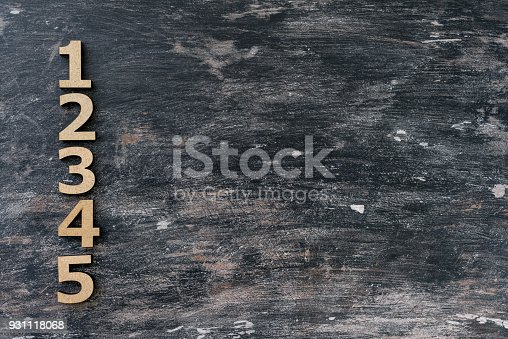 istock Numbers 1, 2, 3, 4, 5 on a dark vintage wooden background. 931118068
