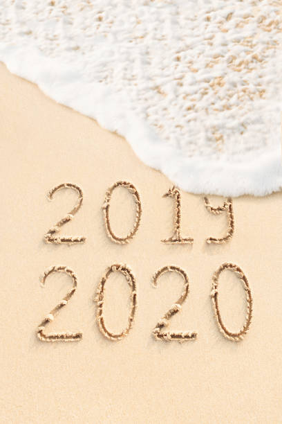 Numbers 2019 and 2020 written in the sand, beach background stock photo