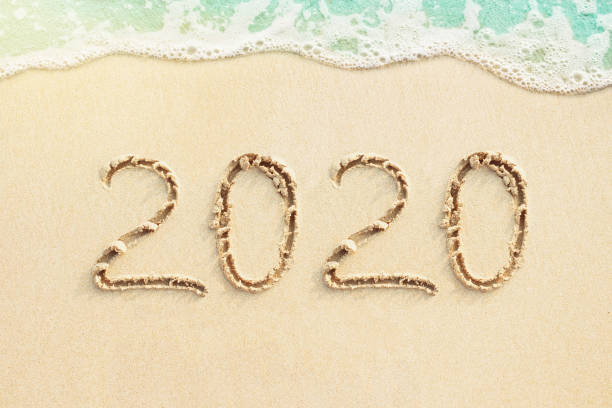 Numbers 2020 written on the sand, beach and blue ocean wave stock photo