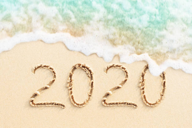 Numbers 2020 written on the sand, beach background stock photo