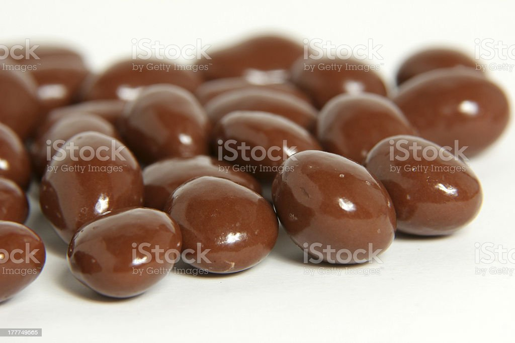 Numerous chocolate covered almonds on a white surface stock photo