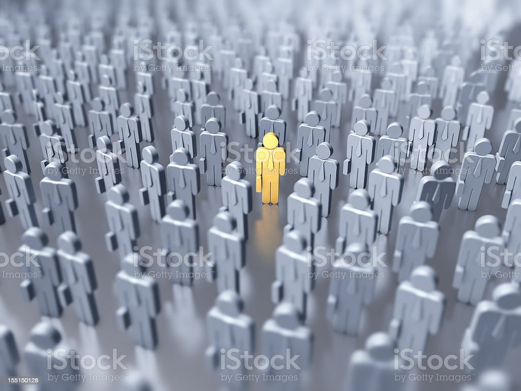 Numerous gray figures with one yellow figure in the middle stock photo