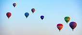 istock Numerous hot air balloons all lift into the air 1277497439