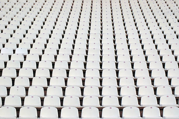 Numerous rows of white stadium seats A field of empty white plastic stadium seats. amphitheater stock pictures, royalty-free photos & images
