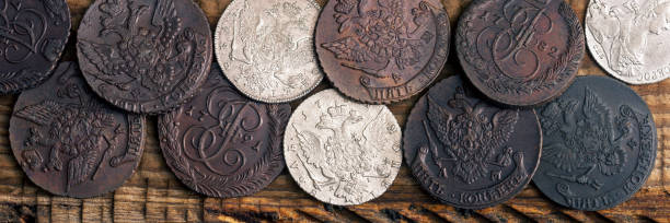 Numismatics. Old collectible coins made of silver, gold and copper on a wooden table. Top view. stock photo