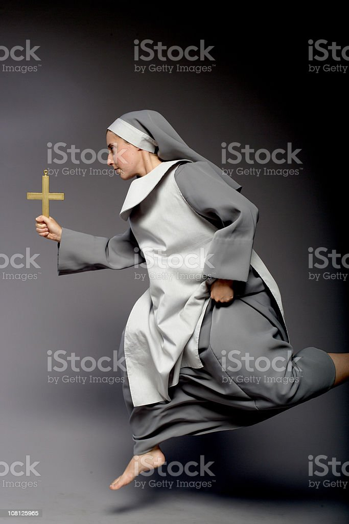 Nun Holding Cross and Running, On Gray Background stock photo