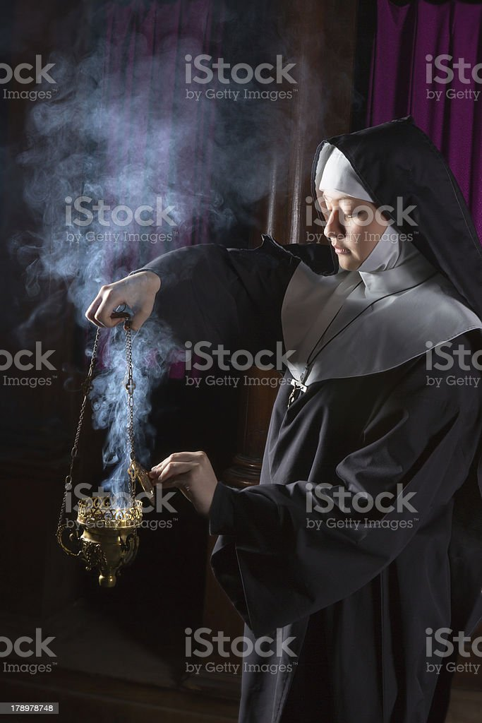 Nun preparing incense for mass royalty-free stock photo