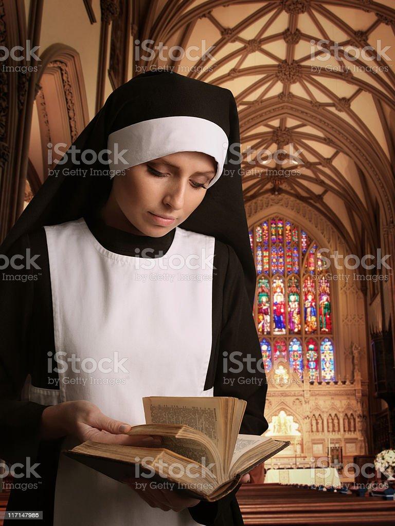 Nun Reading Bible in the Church stock photo