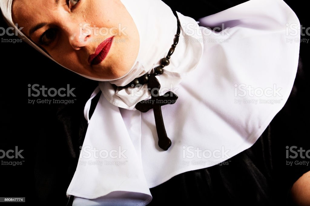 Nun wearing a veil with rosary cross round her neck stock photo