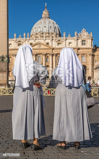 Rome, Italy - September 26, 2014: Two nuns in front of Saint Peter's Basilica.  These two nuns who wear traditional clothes are very modern because one of them use a cell phone while the other admire the basilica.