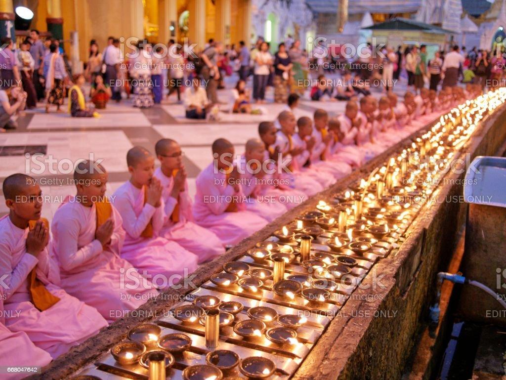 Nuns praying at Shwedagon Pagoda - editorial image stock photo