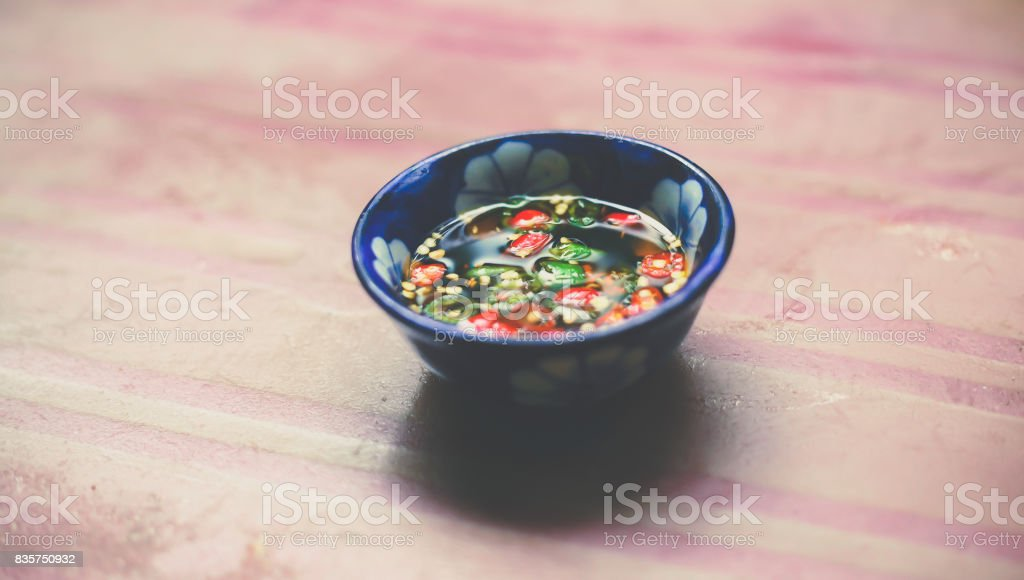 Nuoc Mam - Vietnamese Spicy Fish Sauce in Small bowl on Wooden Background stock photo