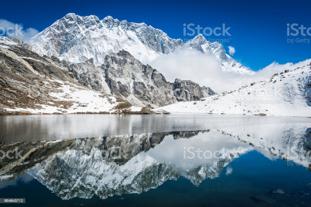 Nuptse 7861m Himalayan mountain peak reflecting in remote lake Nepal stock photo