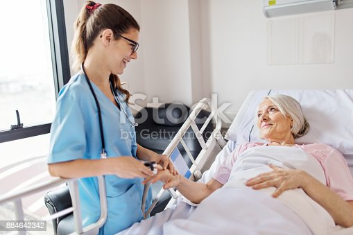 Female nurse adjusting pulse oxymeter on senior woman's finger. Young professional is smiling while looking at patient. Medical worker is examining elderly woman lying on hospital bed.