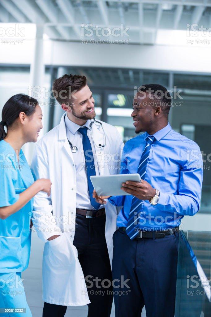 Verpleegkundige en arts een discussie met de zakenman foto