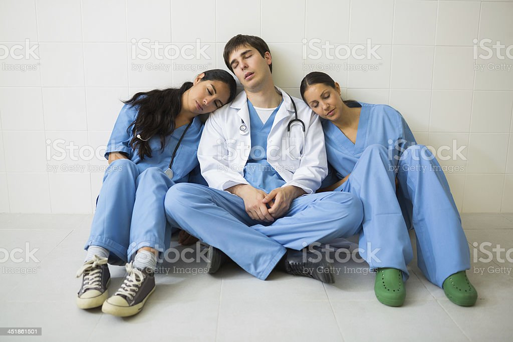 Nurse and doctor sleeping while sitting on the floor stock photo