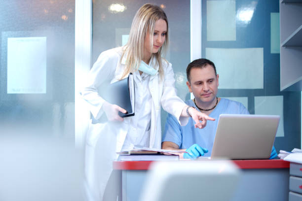 sjuksköterska och läkare använder laptop i medicinsk klinik. - two dentists talking bildbanksfoton och bilder