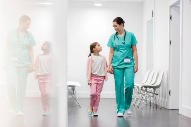 Enfermera y niña paciente caminando en el pasillo en el hospital - foto de stock