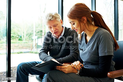 istock Nurse and patient examining application form 574878337