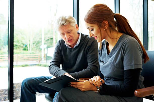 nurse and patient examining application form - two dentists talking bildbanksfoton och bilder