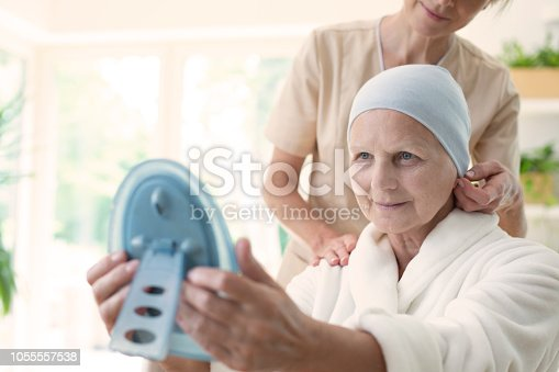 928968772istockphoto Nurse and patient with cancer wearing headscarf and looking at her reflection in the mirror. 1055557538
