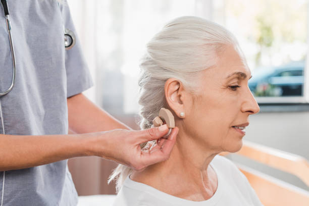 nurse and patient with hearing aid - hearing loss stock pictures, royalty-free photos & images