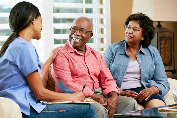 nurse and senior couple talking at a home visit - thuiszorg stockfoto's en -beelden