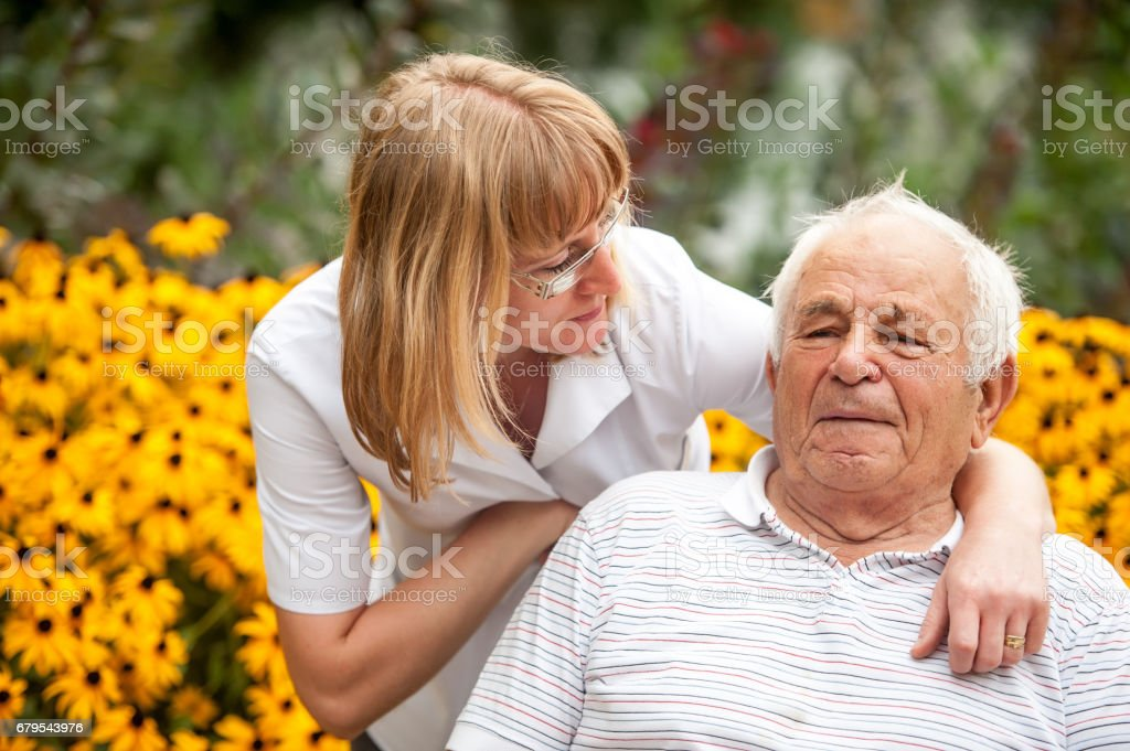 Nurse And Senior Man On Wheelchair Relaxing In The Backyard Of The Retirement Community stock photo