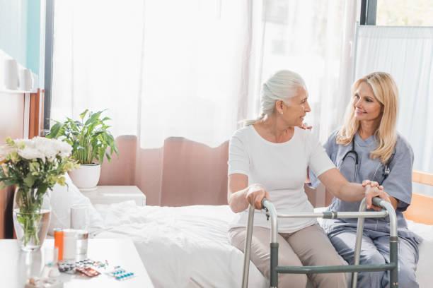 sjuksköterska och senior patient med walker - stötta beskrivande position bildbanksfoton och bilder