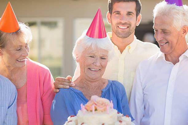 nurse and seniors celebrating a birthday - vorschulgeburtstag stock-fotos und bilder