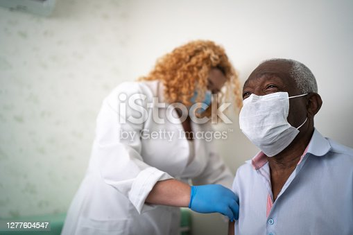 Nurse applying vaccine on patient's arm