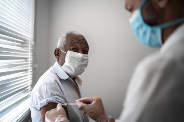 護士用面罩在患者手臂上接種疫苗。 - vaccine 個照片及圖片檔