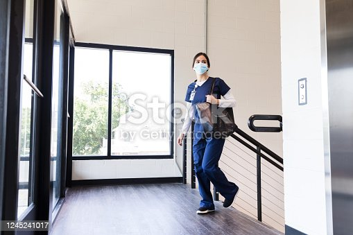 A young adult female nurse arrives for a shift in a hospital. She is wearing medical scrubs and a protective mask.