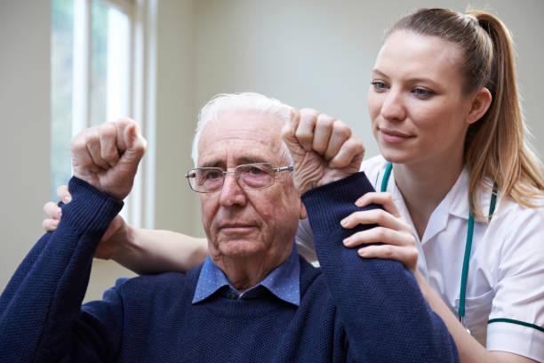 Nurse Assessing Stroke Victim By Raising Arms Nurse Assessing Stroke Victim By Raising Arms paralysis stock pictures, royalty-free photos & images