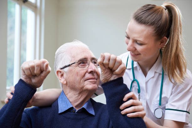Nurse Assessing Stroke Victim By Raising Arms stock photo