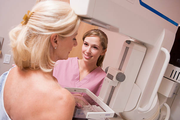 nurse assisting patient undergoing mammogram - screening stock photos and pictures