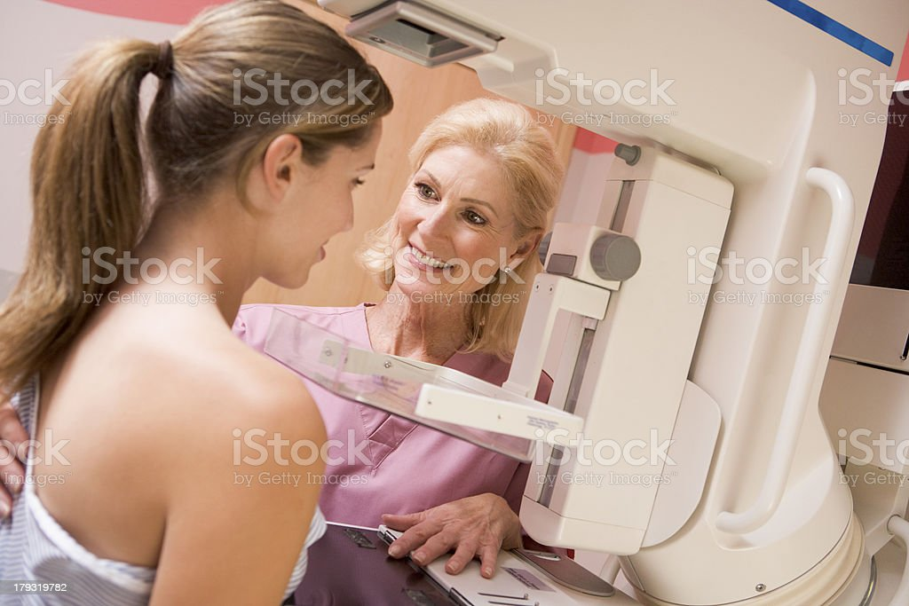 Nurse Assisting Patient Undergoing Mammogram stock photo