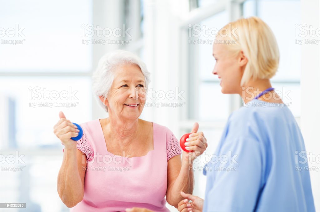 Nurse Assisting Senior Patient In Hand Therapy Balls stock photo