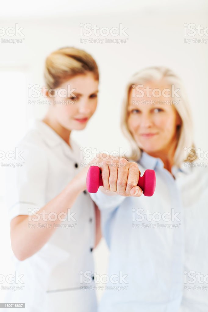 Nurse Assisting Senior Woman In Lifting Weights stock photo