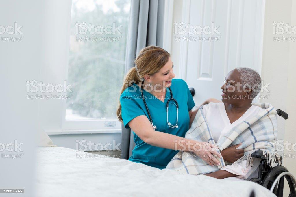 Mature Caucasian nurse assists an elderly woman in a nursing home....